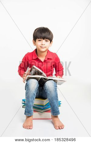 indian Little boy or kid sitting on stack of books while reading a book. Isolated over white