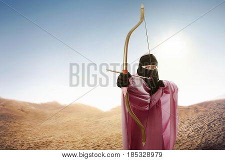 Asian Muslim Woman In Veil Ready To Shoot An Arrow