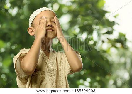 Little Asian Muslim Child In Traditional Dress Praying
