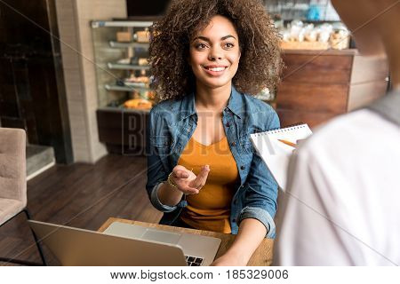Top view of beaming mulatto female speaking with waitress. She sitting at table in cafe