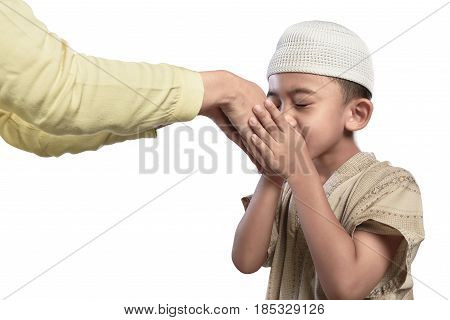 Little Asian Muslim Kid In White Cap Kissing Parents Hand
