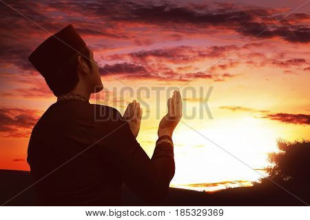 Back View Of Asian Muslim Man With Black Cap Praying