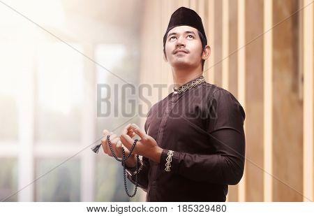Religious Asian Muslim Man In Traditional Dress Using Prayer Beads