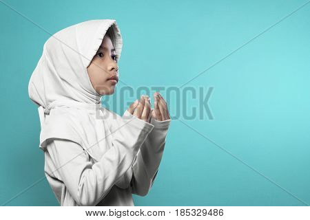Asian Muslim Girl In Hijab Raising Hand And Praying
