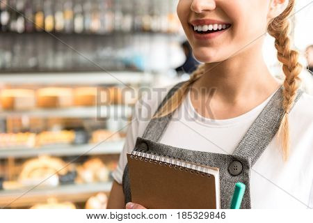 Focus on close up smile of female having job in cafe. She holding scribing-dairy in arms