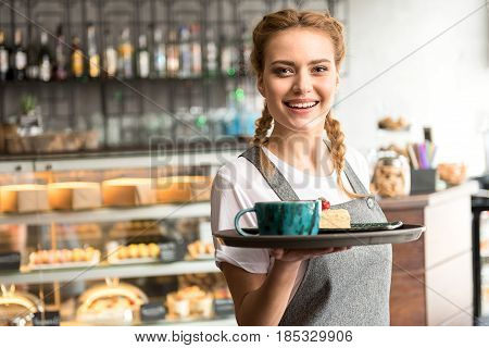 Portrait of cheerful waitress serving on tray cake and cup of beverage in cafe