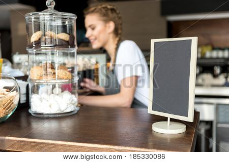 Focus on close up cookies in vases and menu board locating on table in confectionary shop. Waitress is working on background