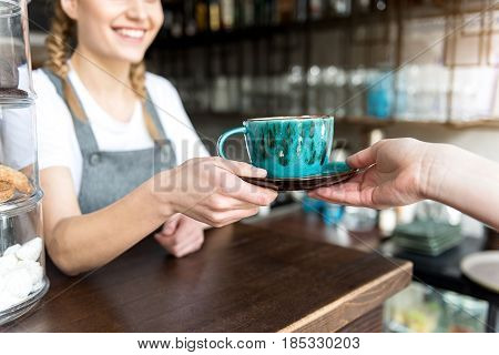 close up arm of cheerful barista holding out mug of appetizing beverage to visitor. She standing at counter