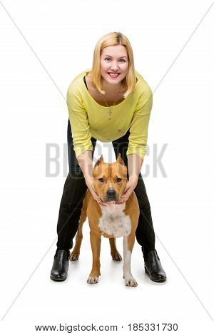 Beautiful happy young woman hugging american staffordshire terrier dog. Studio shot isolated on white background. Copy space.