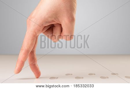 Female fingers walking with footsteps behind them