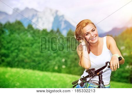 Portrait of a beautiful smiling woman enjoying bright sunny day in the Alps, mountainous tour on bicycle, happy active summer vacation
