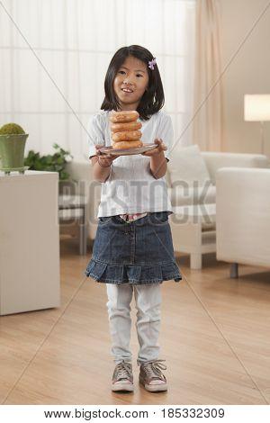 Korean girl holding stack of donuts