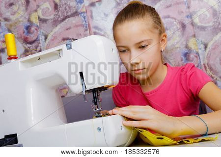A teenage girl diligently learns to sew