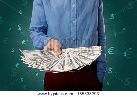 Young businessman holding large amount of bills with green background and currency symbols