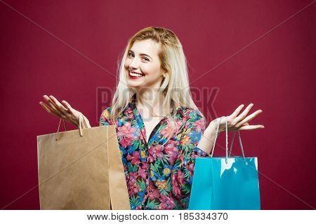Closeup Portrait of Female Shopper Wearing Colorful Shirt is Holding Shopping Bags on Pink Background. Happy Girl with Lond Hair and Charming Smile in Studio.