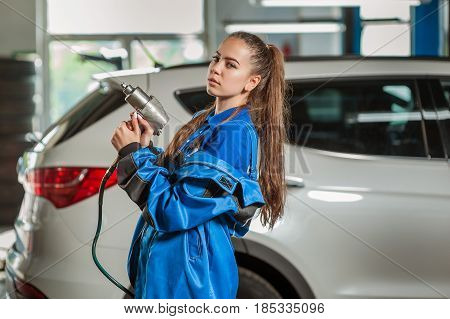 Young beautiful girl at an auto mechanic at work