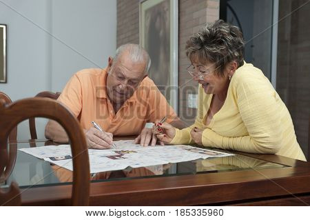 Senior Hispanic couple doing crossword puzzle in newspaper