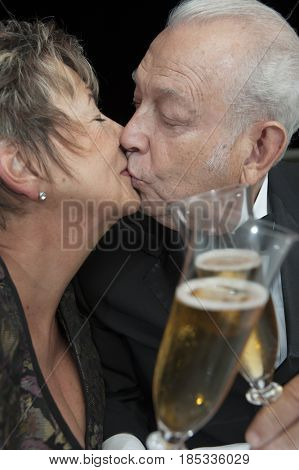 Kissing Hispanic couple toasting with Champagne
