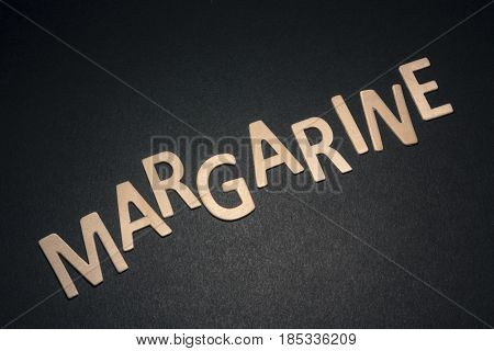 Margarine written with colorful wooden letters on a black background to understand the concept of nutrition and advertising