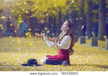 Beautiful Girl With Yellow Leaves In Nami Island, Korea. Nami Island In Autumn. Vintage Tone Style.(