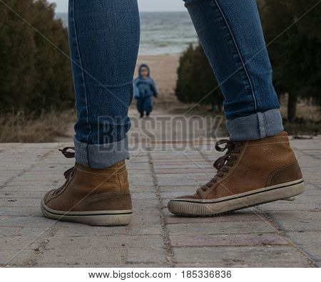 Legs of the girl in brown sneakers and jeans walking along the avenue towards the sea towards the child running towards her