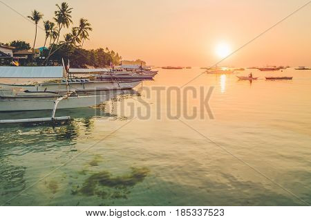 Sunset on the beach with silhouette of banca boat at Panglao Island, Bohol, Philippines.