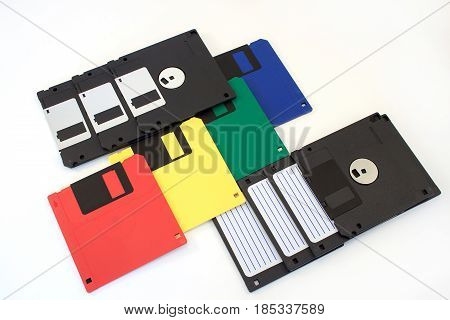 Group of multi-coloured floppy disks on the white background. Retro style.