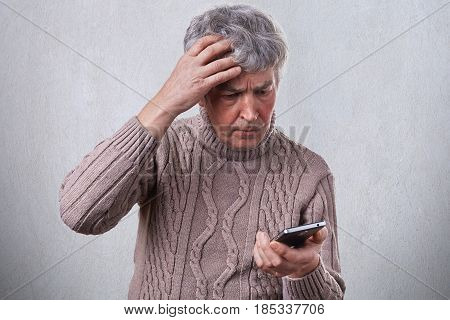 A Troubled Mature Man Holding His Hand On His Gray Head While Using Smartphone Reading Some News In