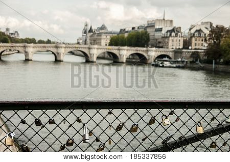 Locks that hang on the railing on the bridge over the Seine in Paris