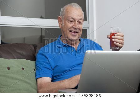 Senior Hispanic man holding drink and using laptop
