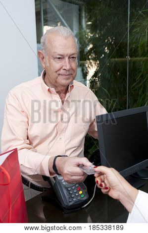Senior Hispanic may paying with credit card