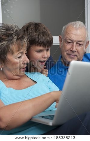 Hispanic grandparents and grandson looking at laptop