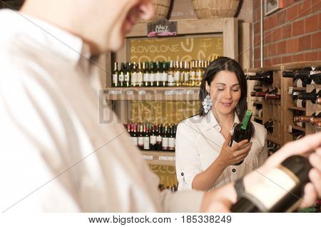 Hispanic woman looking at wine in wine shop