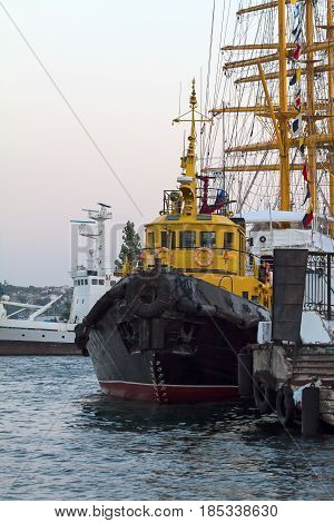 Ship tugboat yellow on the pier at the seaport against other ships. (Sevastopol)