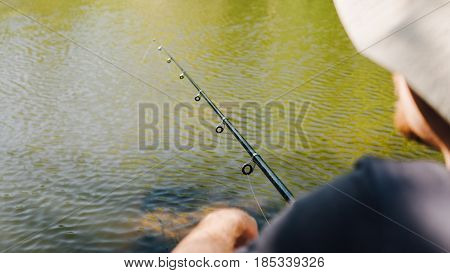 Fishing Rod In Men's Fisherman's Hand Close-up. Fishing In A Wild Place In Nature. A Passion For Fis
