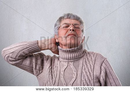 A Mature Man Wearing Warm Sweater And Eyeglasses Holding His Hand On The Neck Being Tired After Work