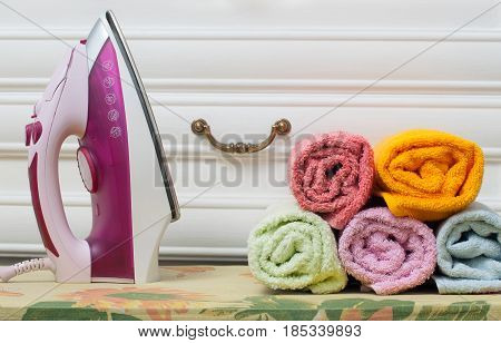 Ironing board with colorful towels on white background. Terry towels