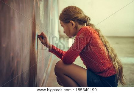 Portrait of child blonde girl drawing at studio