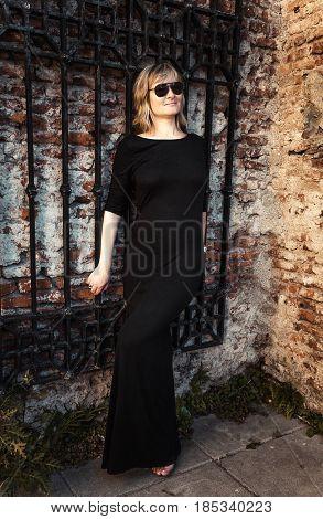 Stylish woman near a textured wall