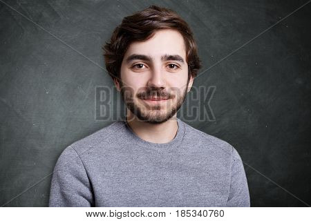 Studio Portrait Of Fashionable Bearded Man Wearing Grey Casual Sweater Looking Pleased Into The Came