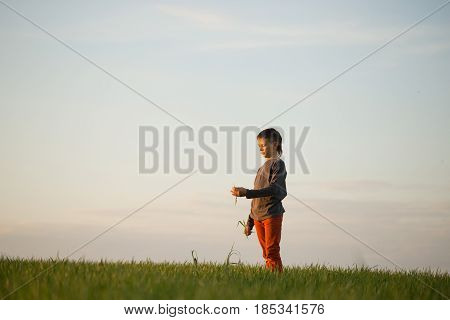 The Teenager Is Standing In The Tall Grass At Sunset