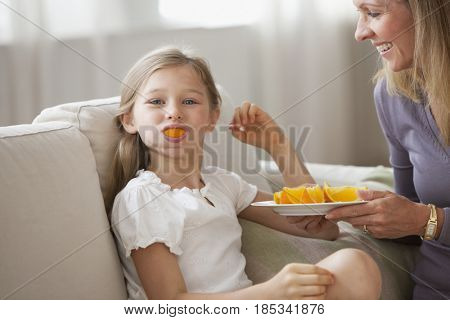 Playful Caucasian girl with orange slice in her mouth