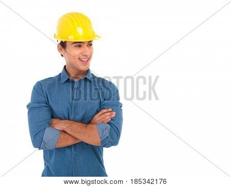 confident construction engineer smiles and looks away to side while holding his hands crossed on white background