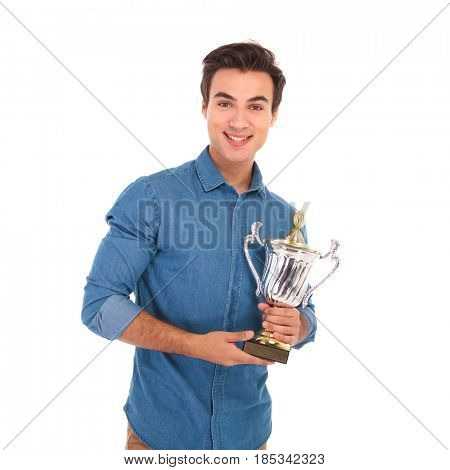 happy young winner holding his trophy prize and smiles on white background