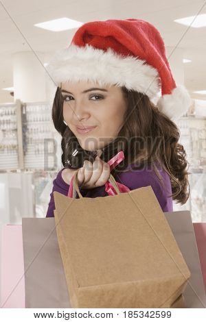 Hispanic teenage girl in Santa hat holding shopping bags