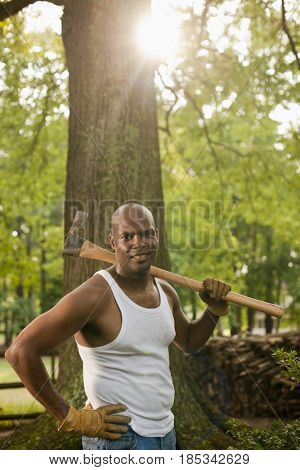 African American man holding ax in backyard