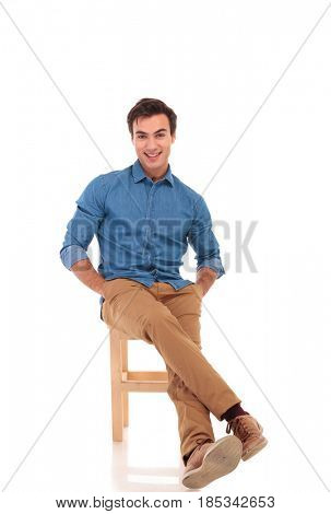happy seated man with hands in pockets is laughing on white background, full body picture