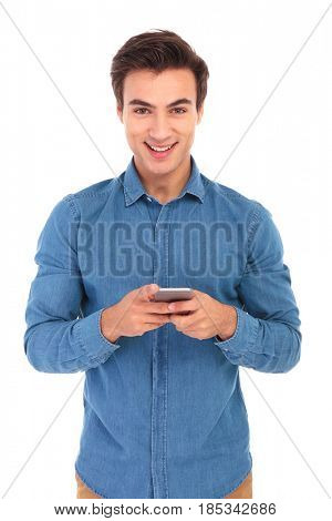 smiling young casual man texting on his mobile phone on white background