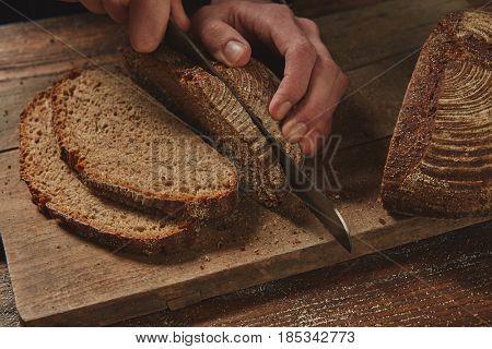 male chef's hand cutting Rye bread