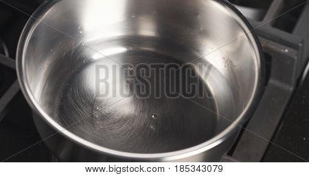 Handheld shot of pouring water into saucepan, 4k photo